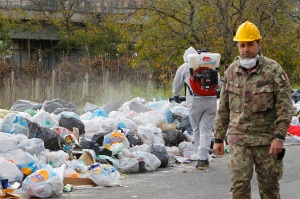 Italian soldier walks past a pile of garbage in Quarto near Naples
