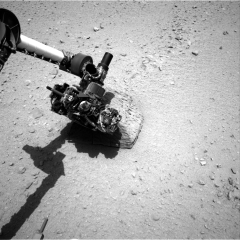 This image shows the robotic arm of NASA's Mars rover Curiosity with the first rock touched by an instrument on the arm.