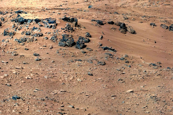 "This patch of windblown sand and dust downhill from a cluster of dark rocks is the ""Rocknest"" site, which was the location for the first use of the scoop on the arm of Curiosity."
