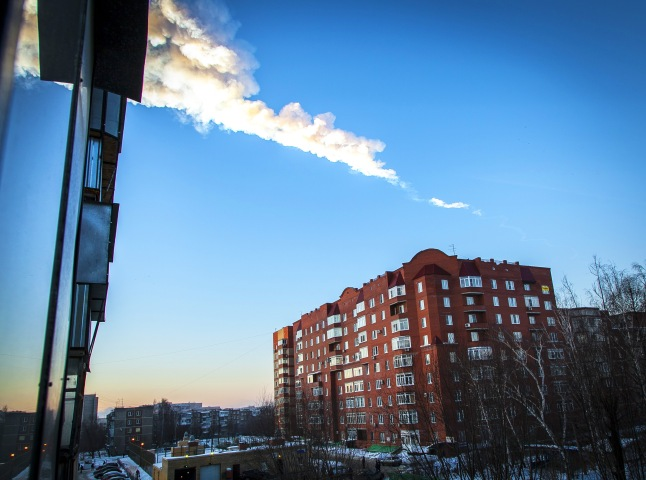 A meteorite trail is seen above a residential apartment block in the Urals city of Chelyabinsk, Russia.