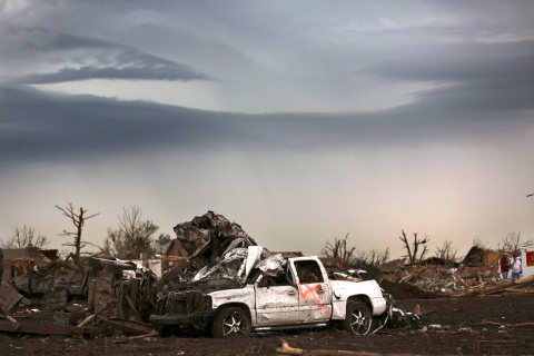 A mangled car rest amongst leveled homes and stripped trees the day after a killer tornado hit in Moore, Okla., May 21 , 2013.