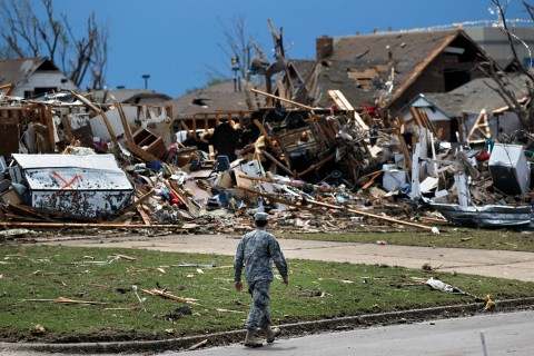 A soldier walks past a home destroyed by the tornado that hit Moore, Okla., the day before, on May 21, 2013.