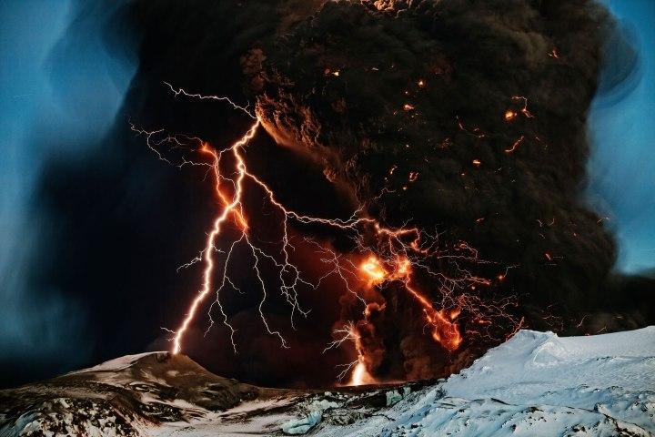 Lightning streaks across the sky as lava flows from a volcano in Eyjafjallajokul