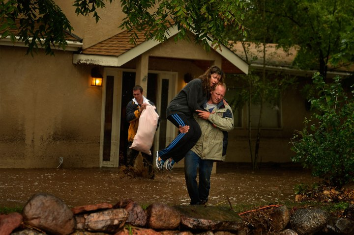 Kyle Schuler carries his wife Cheryl from their home after salvaging what they in Boulder, Colo., Sept. 12, 2013.