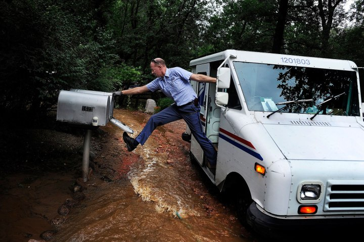 Dave Jackson closes a mailbox with his foot after delivering the mail to a home surrounded on three sides by a flooded Cheyenne Creek in Colorado Springs, Colo., Sept. 13, 2013.