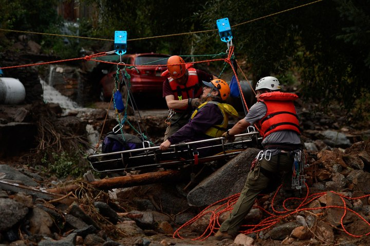Darian Shaw of Salina being rescued by the Alpine Rescue Team using a high line and a sling across 4 Mile Canyon, she was brought across the rushing water with 3 other neighbors. The Alpine Rescue Team, 4 Mile Fire and the Rocky Mountain Rescue Team worked to get people out after heavy rains caused flash flooding and washed away most of Salina, Colo. in 4 Mile Canyon Sept. 13, 2013.