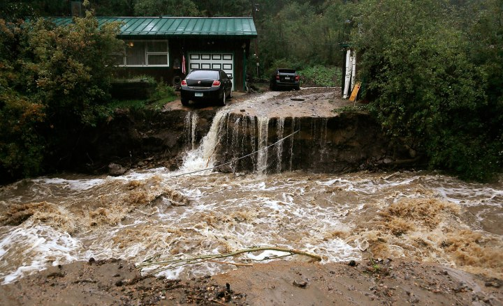 A home and car are stranded after a flash flood in Coal Creek destroyed the bridge near Golden, Colo., Sept. 12, 2013.