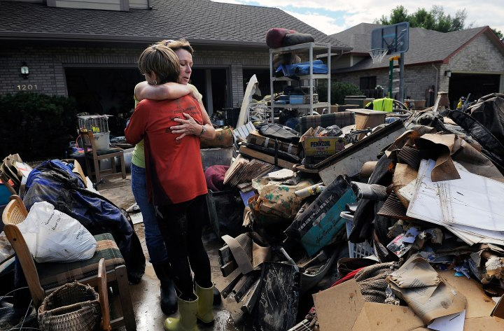 Homeowner Chris Ringdahl is comforted by family friend Katherine MacIntosh in front of her possessions as they cleanup from the floodwaters in Longmont, Colo., Sep. 16, 2013.