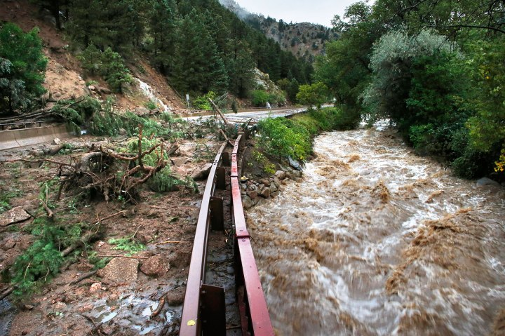 Boulder Creek flows at high speed next to a road closed off by debris from days of rain and flooding, at the base of Boulder Canyon, Colo., on Sept. 13, 2013.