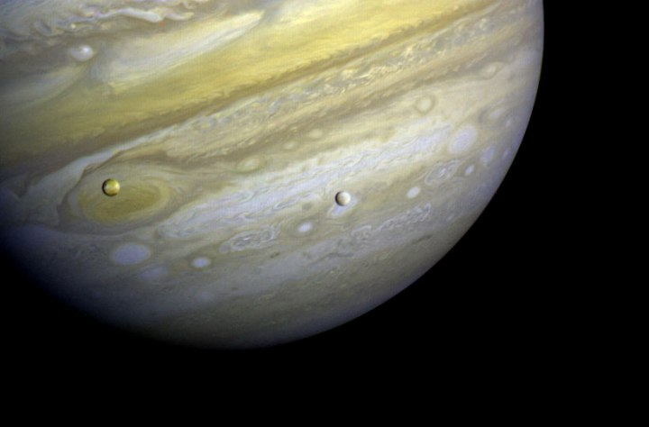 Jupiter and two of its satellites (Io, left, and Europa) on Feb. 13, 1979. Io is about 350,000 kilometers (220,000 miles) above Jupiter's Great Red Spot; Europa is about 600,000 kilometers (375,000 miles) above Jupiter's clouds.
