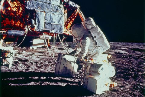 An Apollo 12 astronaut places an Apollo Lunar Surface Experiments Package on the Moon.