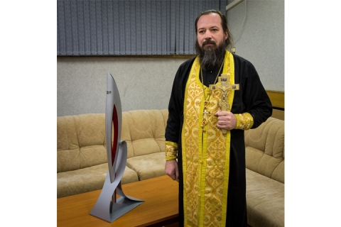 Orthodox priest, Father Sergei, with the 2014 Sochi Olympic torch before it launched with Expedition 38 Soyuz Commander Mikhail Tyurin of Roscosmos, Flight Engineer Koichi Wakata of the Japan Aerospace Exploration Agency, and, Flight Engineer Rick Mastracchio of NASA, on Nov. 7, 2013, in Baikonur, Kazakhstan.