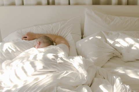 Man sleeping in bed with morning light