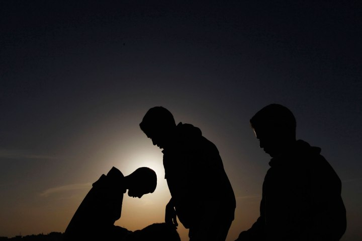 People observe a solar eclipse in Amman, on Nov. 3, 2013.