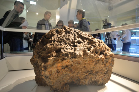 Reporters gather around a piece of a meteorite, which was lifted from the bottom of the Chebarkul Lake, placed on display in a local museum in Chelyabinsk, on Oct. 18, 2013.