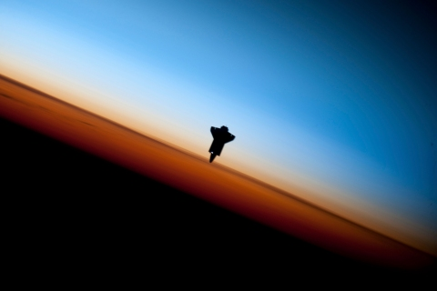 The space shuttle Endeavour is silhouetted against the backdrop of Earth's horizon prior to docking with the International Space Station