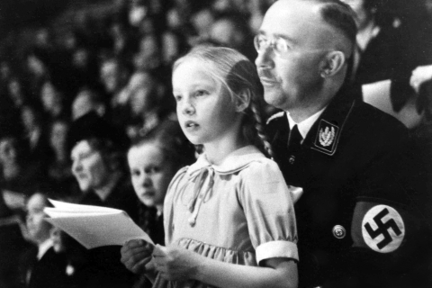From right: Chief of the German Police and Minister of the Interior Heinrich Himmler with his daughter Gudrun on his lap watch an indoor sports display in Berlin, on March 6, 1938.