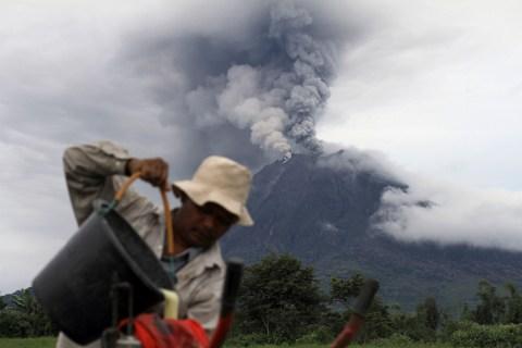 A villager flows pesticide into his bowl as Mount Sinabung spews ash at Kebayaken village in Karo district