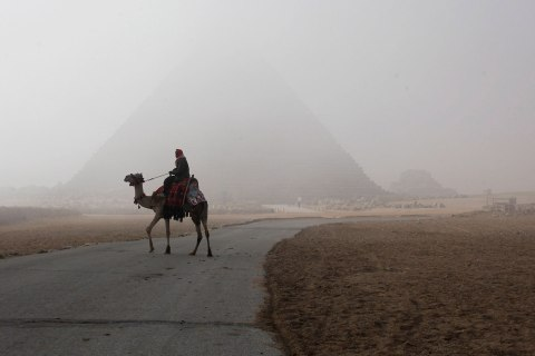 A man rides his camel as he waits for tourists at the Giza pyramids area, south of Cairo